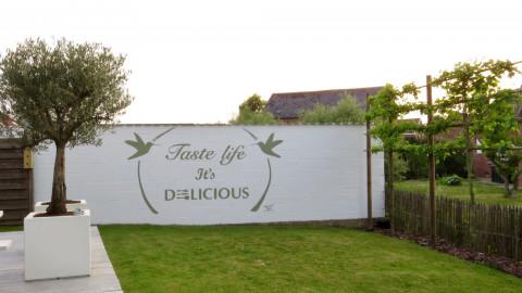 Muurschildering tekst buiten tuin
